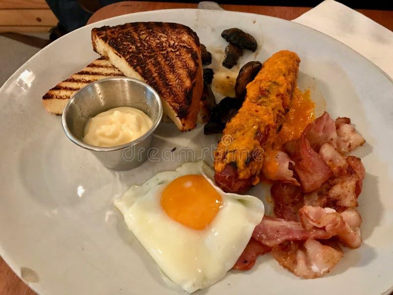 热的早餐板材用香肠、荷包蛋、烟肉和多士面包/英国样式 免版税库存照片