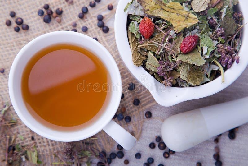 热的杯子与白色灰浆的草本和黑莓茶与杵 免版税库存照片