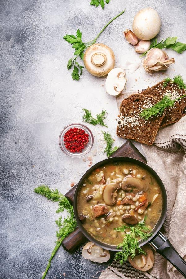 热的浓蘑菇汤用牛肉、香料和整粒大麦,肉汤 用黑面包,在金属平底锅,顶视图,平的位置, 免版税库存图片