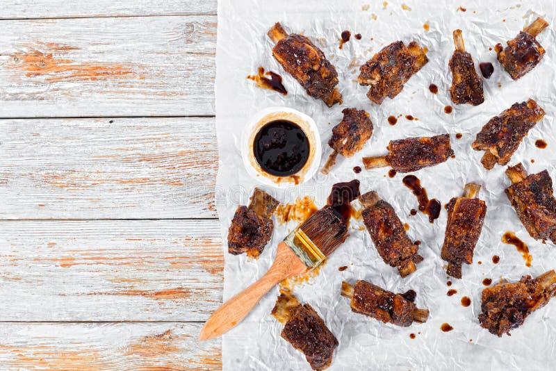 热的稠粘的肋骨晒干了用在羊皮纸的烤肉汁 免版税库存照片