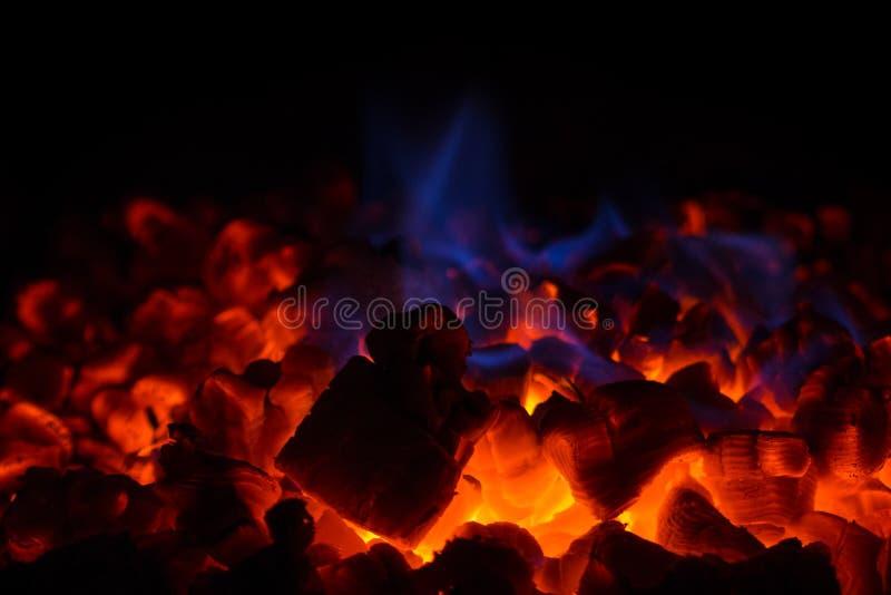 热的红色炭烬和蓝焰特写镜头在壁炉 免版税图库摄影