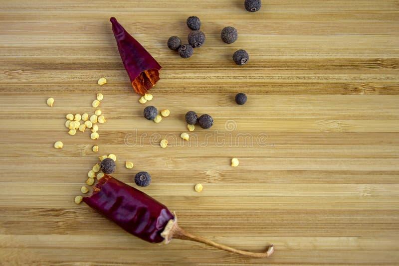 热的红辣椒,多香果打破的荚  库存图片