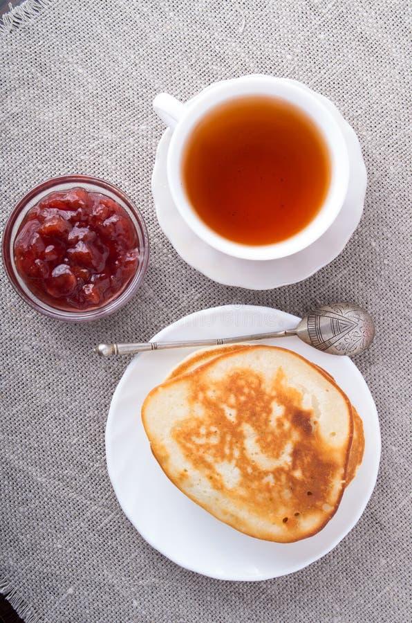 热的薄煎饼、茶和草莓酱板材顶视图  免版税库存照片