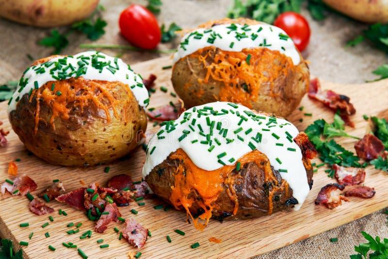 热的被烘烤的土豆用乳酪、烟肉、香葱和酸性稀奶油 免版税库存图片