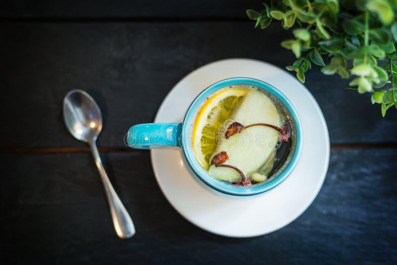热的酒精饮料 威士忌酒用苹果汁和香料茴香,丁香,桂香,在一个蓝色杯子的柠檬 库存照片