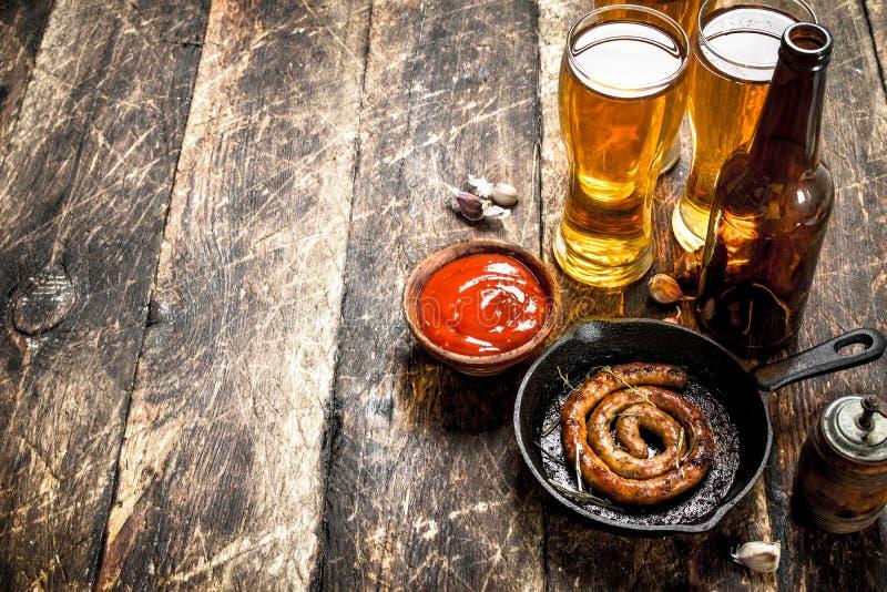 热的香肠用冰镇啤酒 库存图片