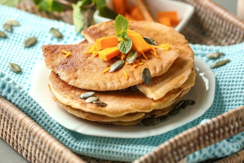 热的鲜美薄煎饼用在柳条盘子的南瓜 免版税库存照片
