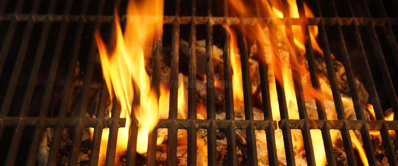 热的BBQ格栅、明亮的火焰和灼烧的煤炭 免版税图库摄影