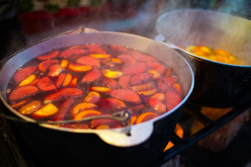 热的gluhwein或被仔细考虑的酒在一口大锅在相当,地方款待,温暖和辣 在市场的一份热的健康的传统柑橘饮料 免版税库存照片