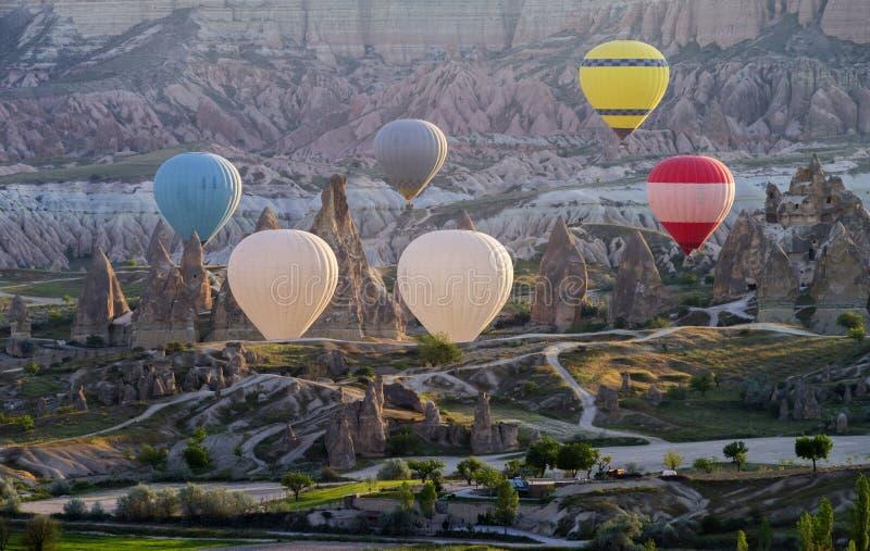 热空气在令人惊讶的风景的气球飞行在日出,卡帕多细亚土耳其 免版税库存照片