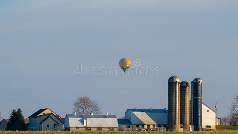 热空气气球漂浮在一个门诺派中的严紧派的农厂房子上的,兰开斯特县,PA 库存照片