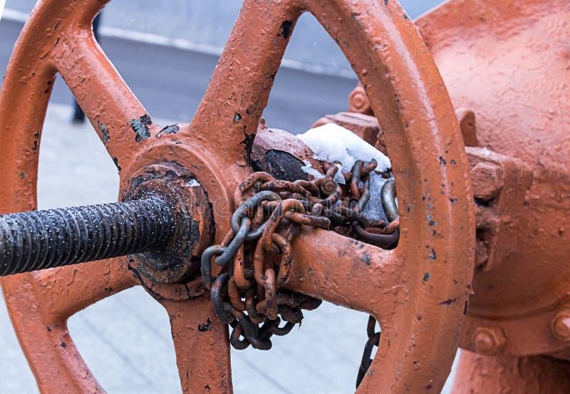 热系统的老生锈的饱经风霜的圆的阀门零件与一个长的螺栓的有链子的敲响工业设计基地 免版税库存图片