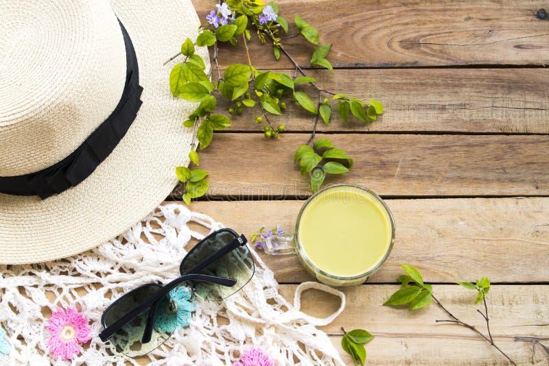 热草本健康的饮料挤奶与帽子,太阳镜的绿茶,编织羊毛 免版税库存照片