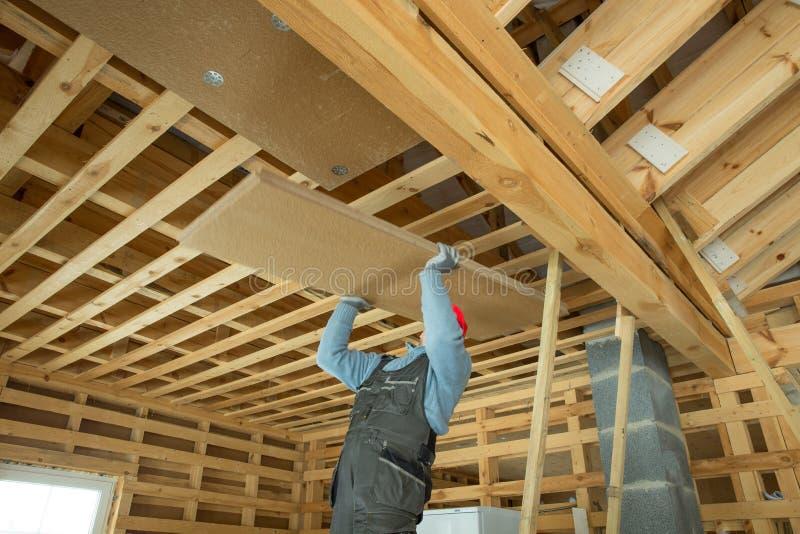 热量地绝缘eco木制框架房子的建筑工人 免版税库存图片