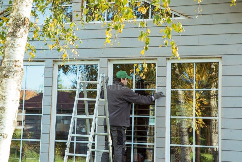 热量地绝缘eco木制框架房子的建筑工人 免版税图库摄影