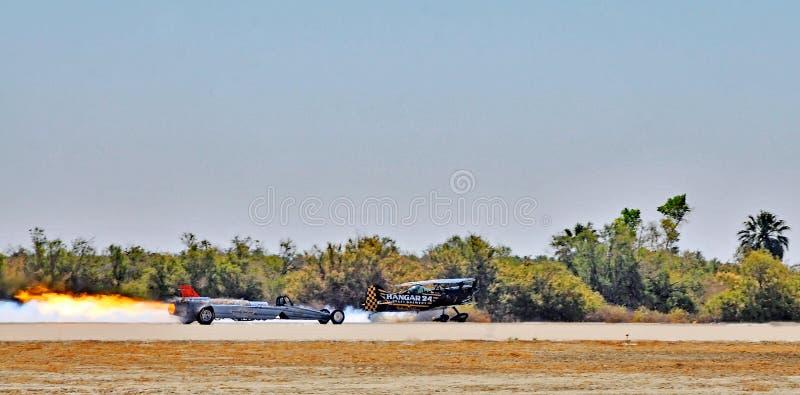 热量飞行表演:跑引擎的Dragster &双翼飞机 免版税库存图片
