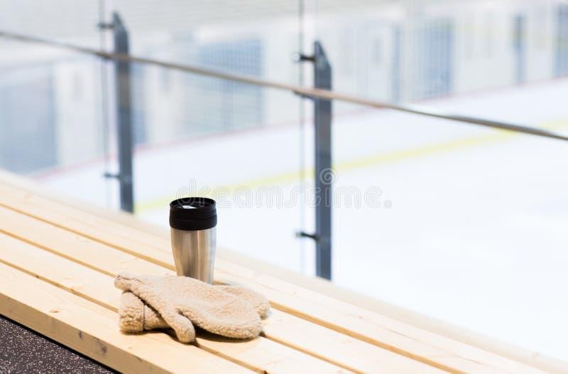 热水瓶杯子和手套在长凳在滑冰场竞技场 免版税库存图片
