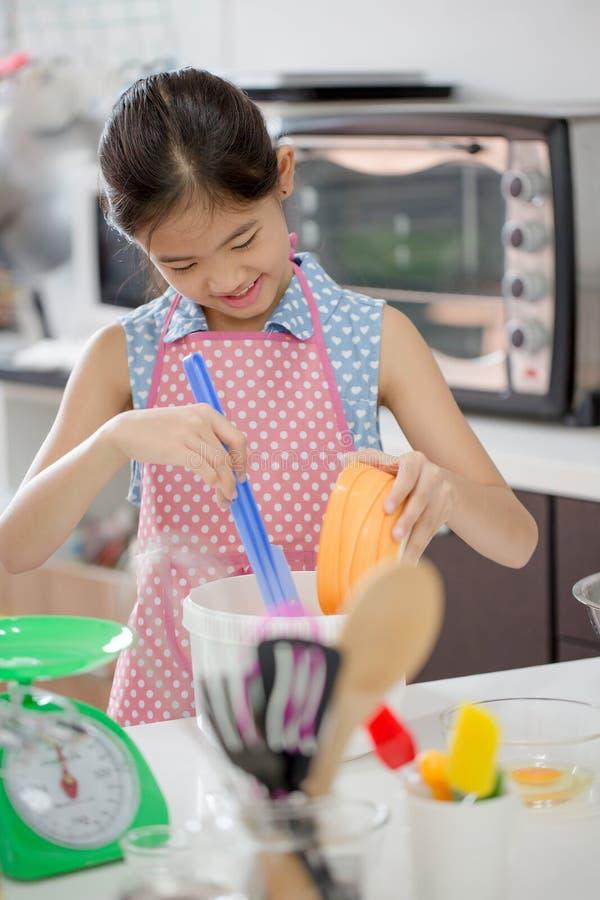 烹调一个面包店的小亚裔逗人喜爱的厨师在厨房里 免版税库存照片