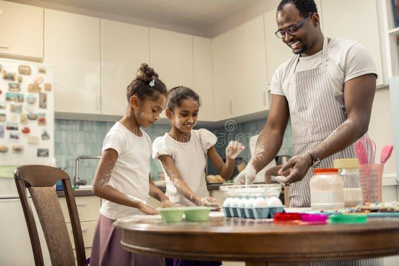 烹调与他们爱恋的有用的父亲的两个滑稽的女孩饼 库存图片