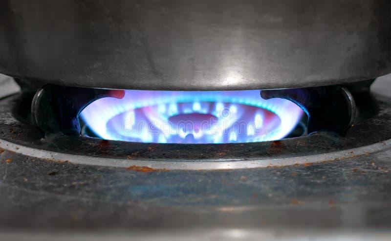 烹调与充分的火焰的肮脏的老天然气火炉  免版税库存图片