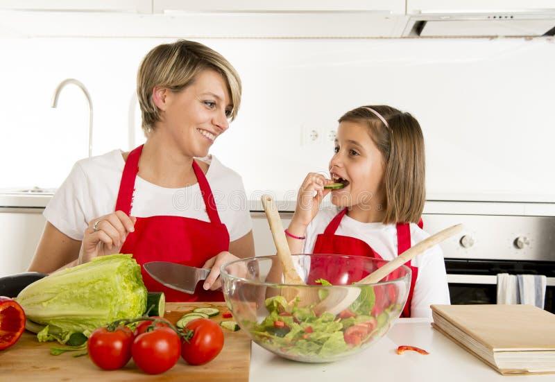 烹调与厨师围裙一起的母亲和小女儿在家准备沙拉厨房 图库摄影