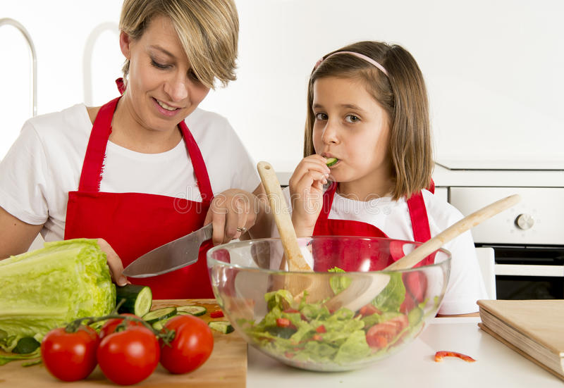 烹调与厨师围裙一起的母亲和小女儿在家准备沙拉厨房 免版税库存图片