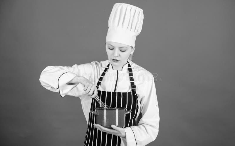 烹调与启发 搅拌调味汁或奶油甜点在烹调的逗人喜爱的厨师罐 俏丽的与导线飞奔的厨师纯奶油 免版税库存图片