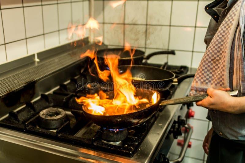 烹调与在一个煎锅的火焰的餐馆厨师在厨灶 免版税库存照片