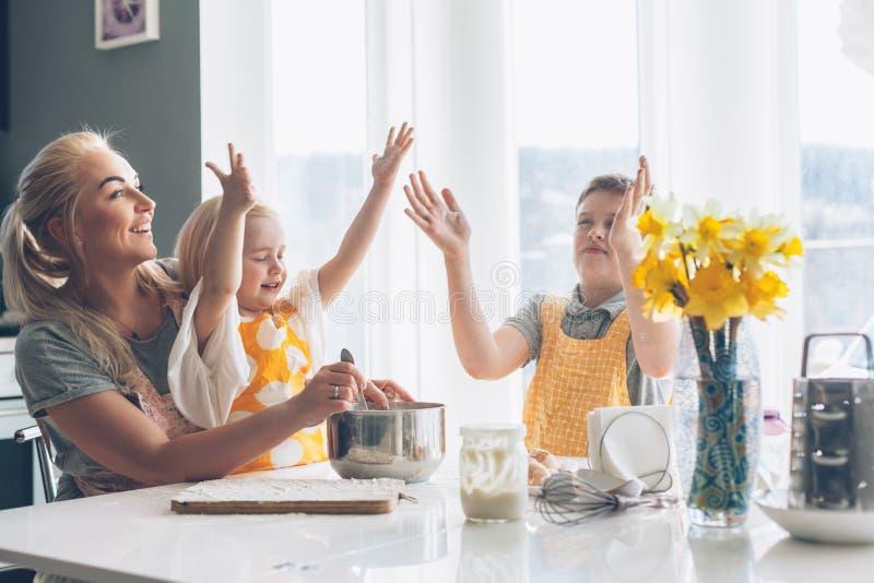 烹调与在厨房的孩子的妈妈 免版税库存图片