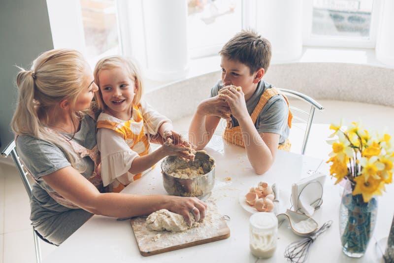 烹调与在厨房的孩子的妈妈 库存照片