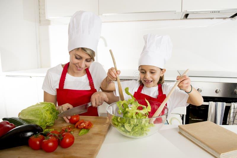 烹调与帽子围裙一起的母亲和小女儿在家准备沙拉厨房 库存图片
