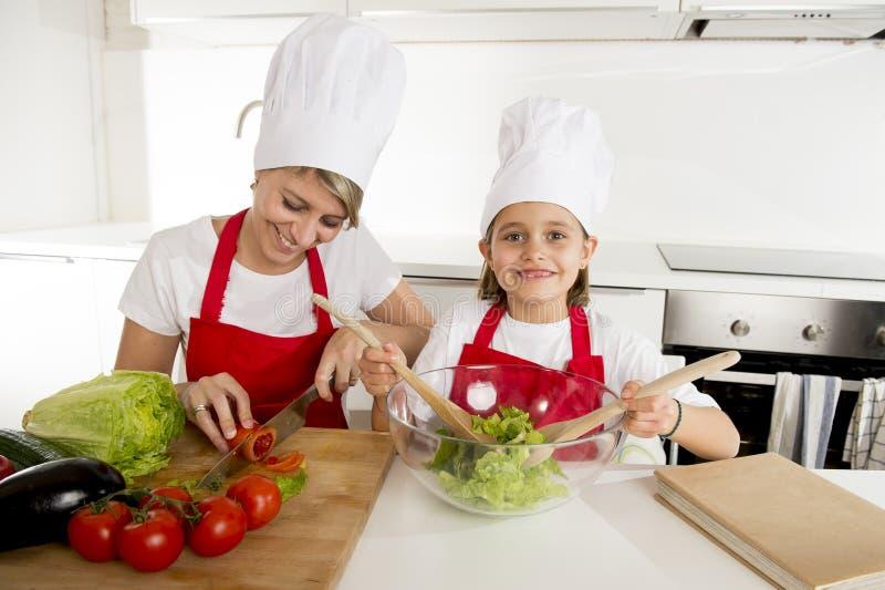 烹调与帽子围裙一起的母亲和小女儿在家准备沙拉厨房 免版税库存图片