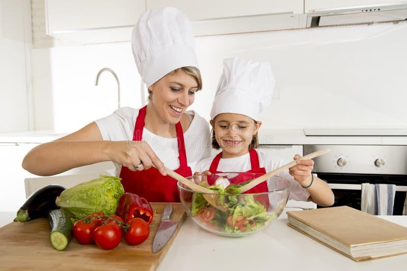 烹调与帽子围裙一起的母亲和小女儿在家准备沙拉厨房 库存照片