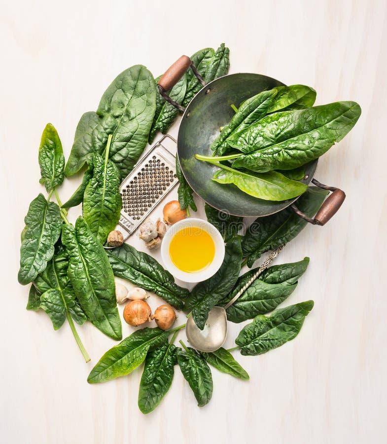 烹调与平底锅、花格和碗的菠菜成份在白色木背景的油 免版税图库摄影