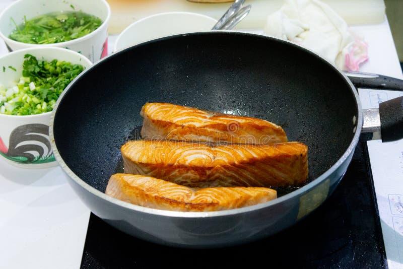 烹调与平底锅的鲑鱼排,油煎鲑鱼排 免版税库存照片