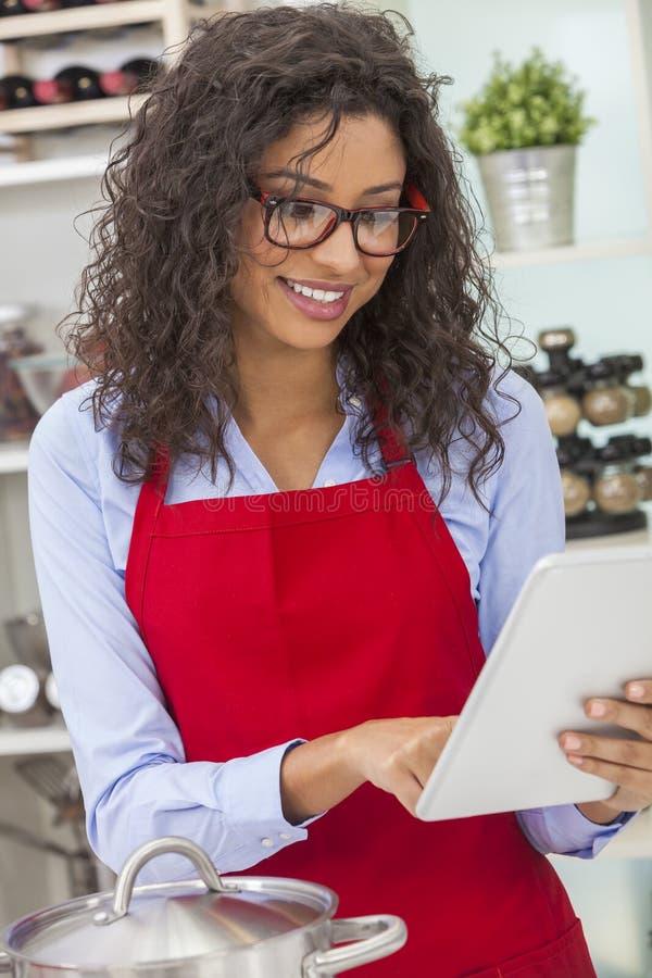 烹调与片剂计算机的愉快的妇女在厨房里 免版税库存图片