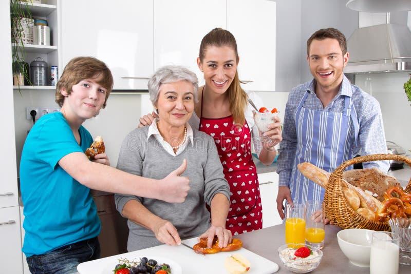 烹调与祖母一起的愉快的家庭。 免版税库存照片
