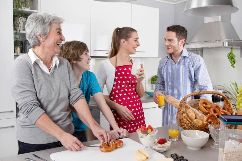 烹调与祖母一起的愉快的家庭。 免版税库存图片