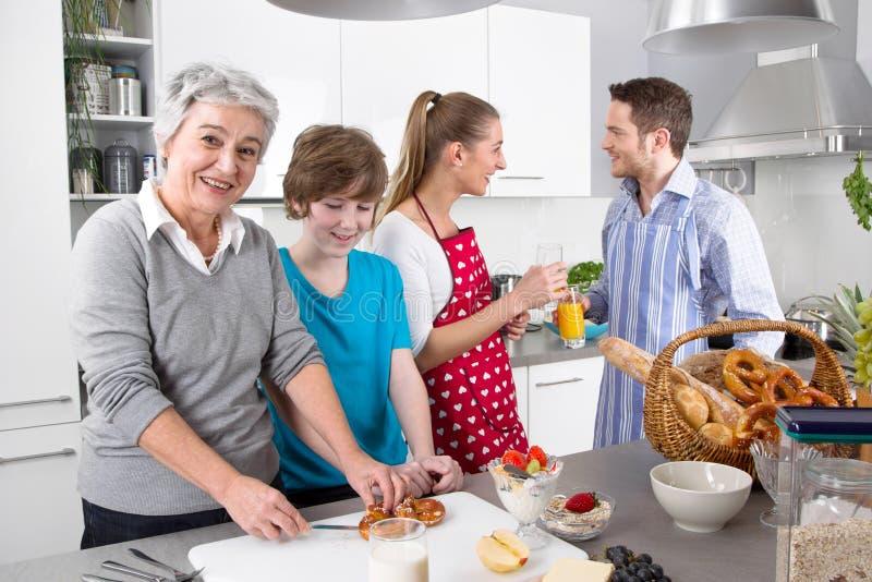 烹调与祖母一起的愉快的家庭 免版税库存照片