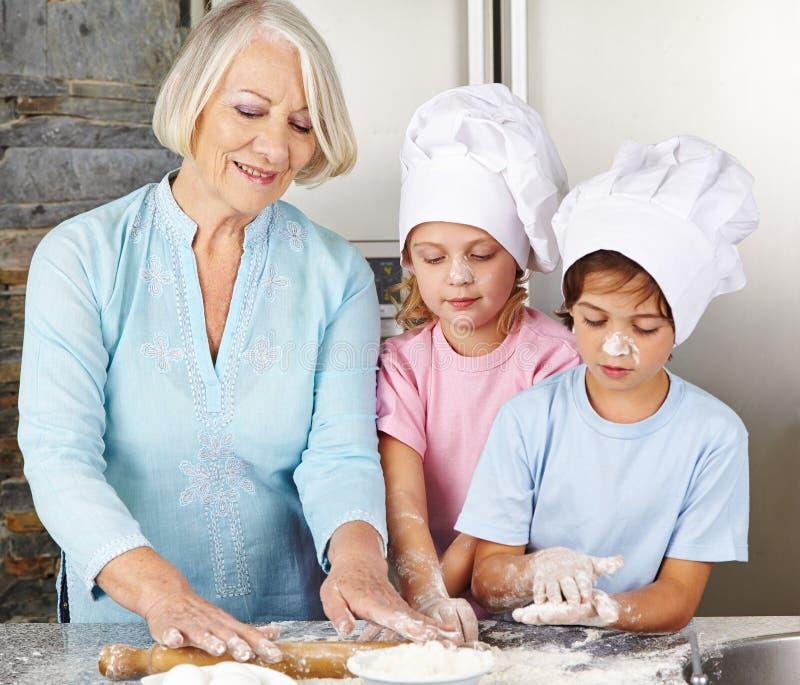 烹调与祖母的孩子 免版税图库摄影