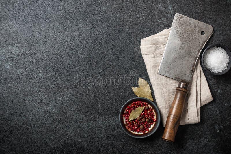 烹调与葡萄酒的背景宰割砍肉刀和香料在bl 免版税库存图片