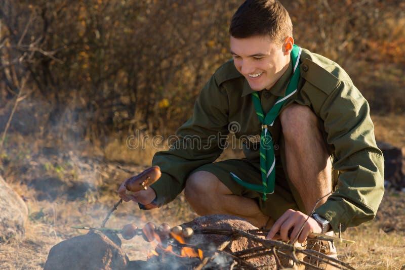 烹调为在地面上的食物的年轻童子军 免版税库存照片