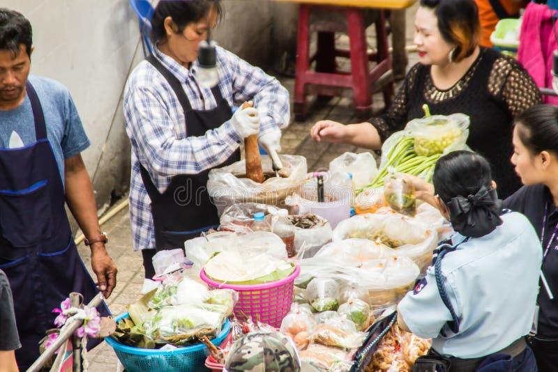 烹调为番木瓜沙拉食物的街头小贩在街道上的待售 绿色番木瓜沙拉是由切细的未成熟做的辣沙拉 图库摄影
