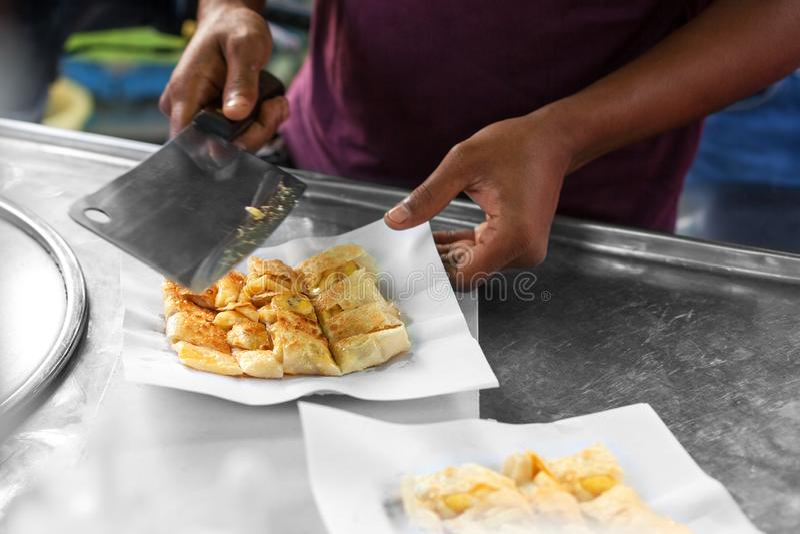 烹调传统泰国油煎的roti香蕉薄煎饼在泰国关闭,亚洲街道食物配制 免版税图库摄影