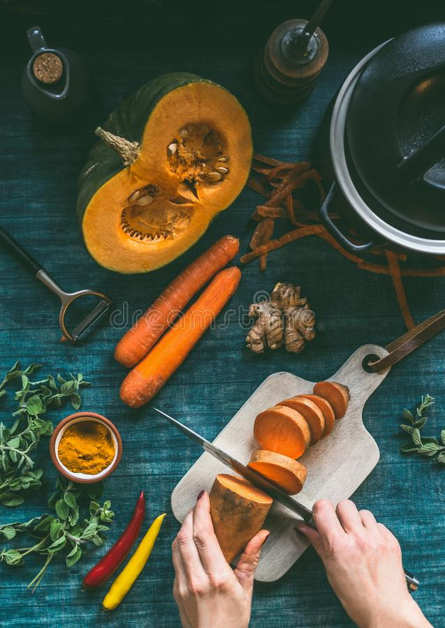 烹调健康汤或菜的女性手炖与橘黄色素食成份:南瓜,红萝卜,地瓜 库存图片