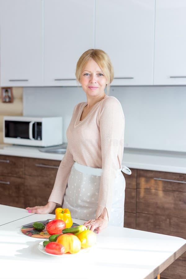 烹调健康食品的资深妇女在房子厨房 库存图片