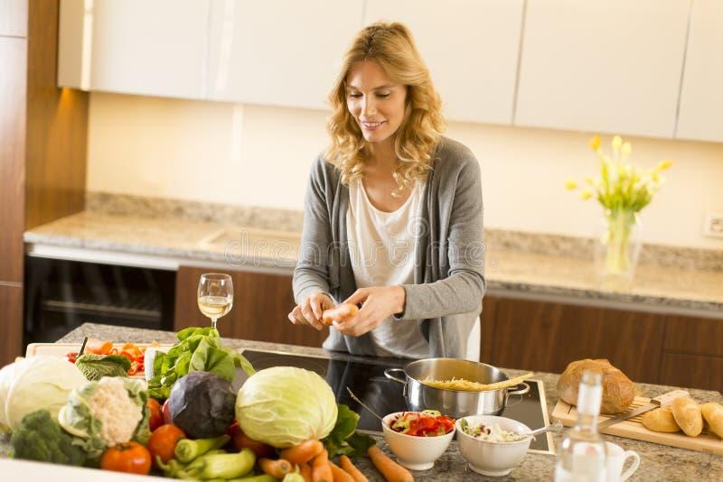 烹调健康食物的少妇在现代厨房里 库存图片