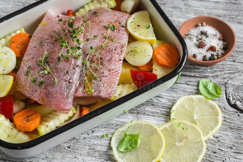 烹调健康食物-未加工的成份:土豆、夏南瓜、红萝卜、葱、大蒜、胡椒和鱼在烘烤盘的鲈鱼 免版税库存照片