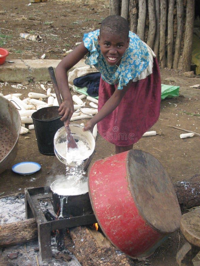 烹调午餐公开的年轻非洲农村女孩 免版税库存照片