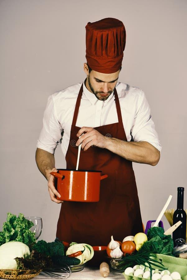 烹调和专业烹调概念 有繁忙的面孔的厨师拿着在灰色背景的红色平底深锅 免版税库存照片